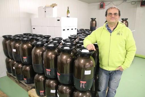 Lelio Bottero con alcuni fusti e contenitori in cartone di birra stoccati nel magazzino