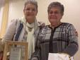 """La presidente Ail Cuneo Elsa Morra (a destra) con la volontaria Ionela Lazard dopo la consegna """"a sorpresa"""" della targa di ringraziamento da parte dei volontari"""
